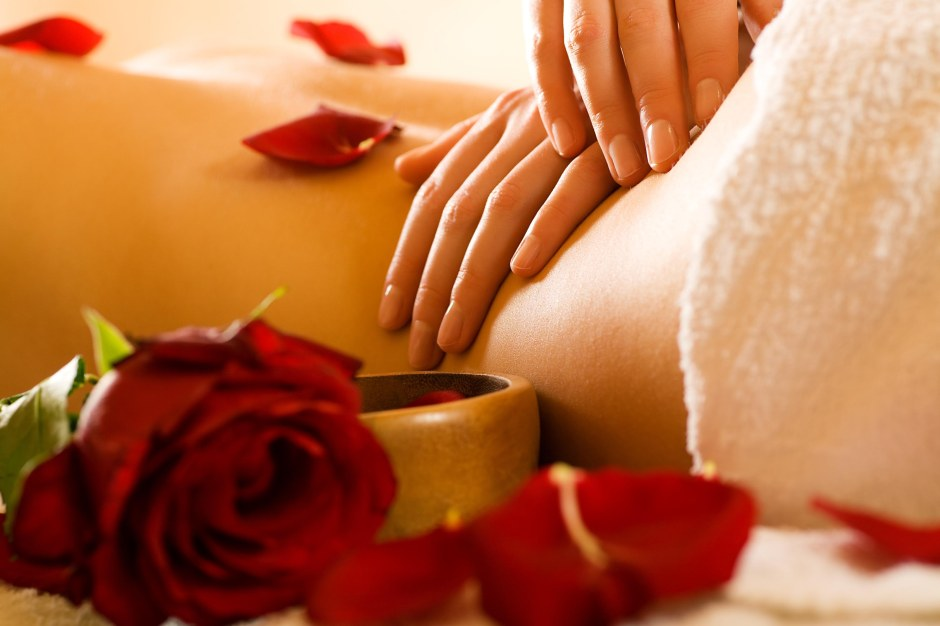 Two hands massaging small of naked woman's back with rose